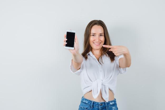 Молодая леди, указывая на телефон в белой блузке и глядя весело, вид спереди.