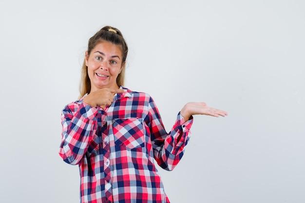 Девушка в клетчатой рубашке, указывая на что-то, выглядела весело. передний план.
