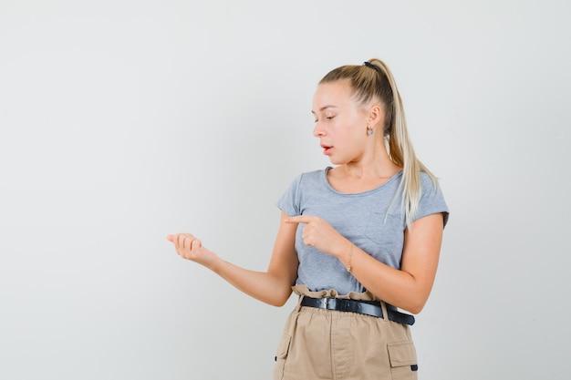 Девушка, указывая на что-то, притворилась, что ее держат в футболке и штанах, и выглядела сосредоточенной