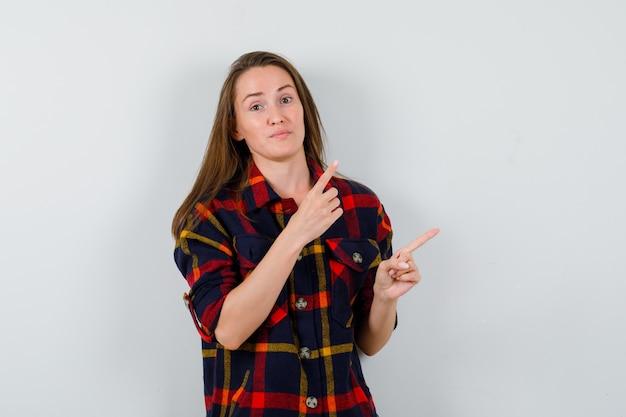 Девушка в нерешительной рубашке, указывая на верхний правый угол. передний план.