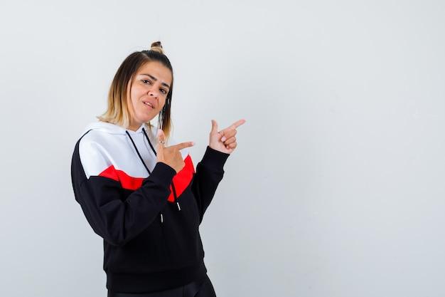 パーカーのセーターの右上隅を指して自信を持って見える若い女性。