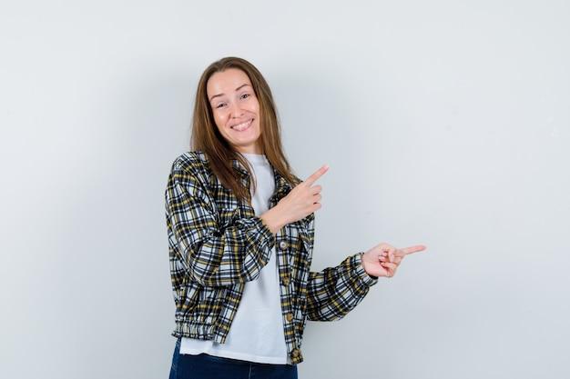 T- 셔츠, 재킷에 오른쪽 상단 모서리를 가리키고 쾌활한 찾고 젊은 아가씨. 전면보기.