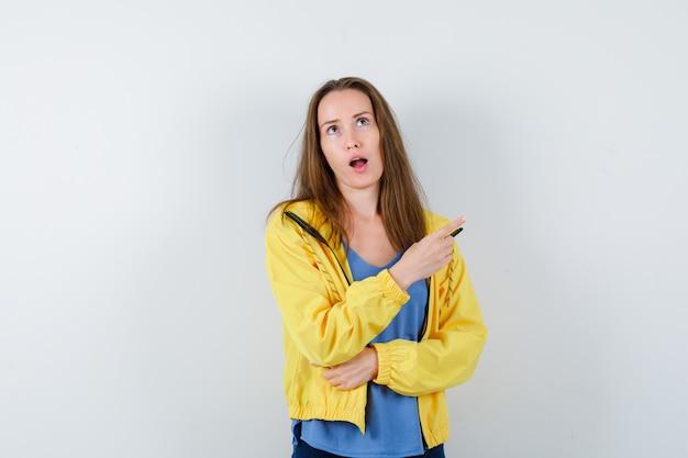 Tシャツ、ジャケット、物思いにふける、正面図で右上隅を指している若い女性。