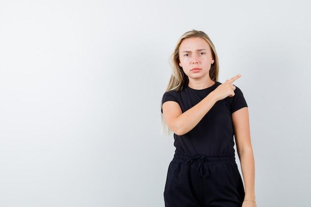 Tシャツ、ズボンで右上隅を指して、体調不良の若い女性。正面図。