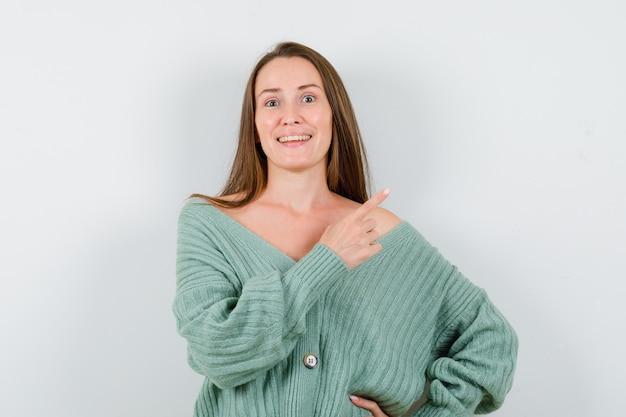 ウールのカーディガンで右上隅を指して、幸せそうに見える若い女性。正面図。