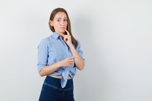 青いシャツ、ズボンを着て、好奇心旺盛な若い女性。