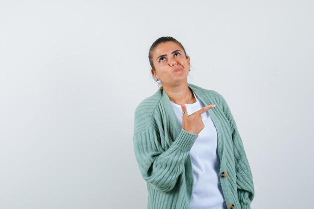 Девушка в футболке, куртке и задумчиво смотрит в сторону