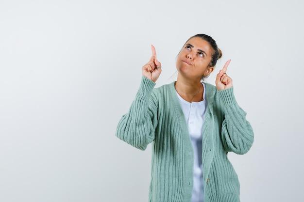 若い女性がtシャツ、ジャケットを指差して物思いにふける