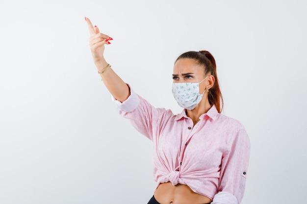 Giovane donna che punta in camicia, maschera e sguardo concentrato, vista frontale.