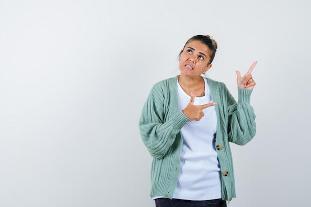 Giovane donna che indica via in maglietta, giacca e sembra pensierosa