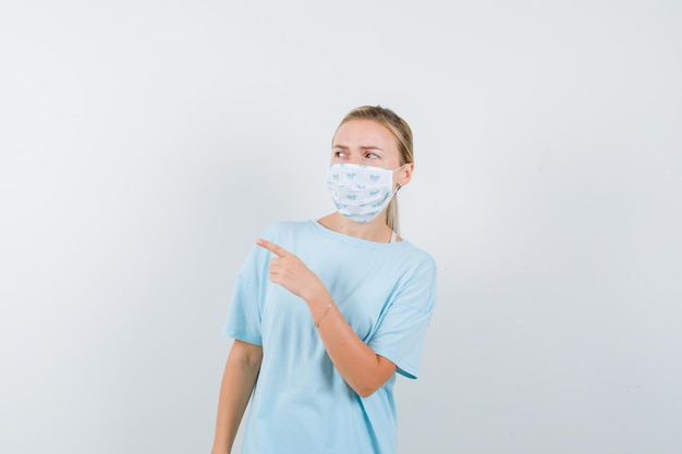 Young lady pointing away in t-shirt, mask and looking focused