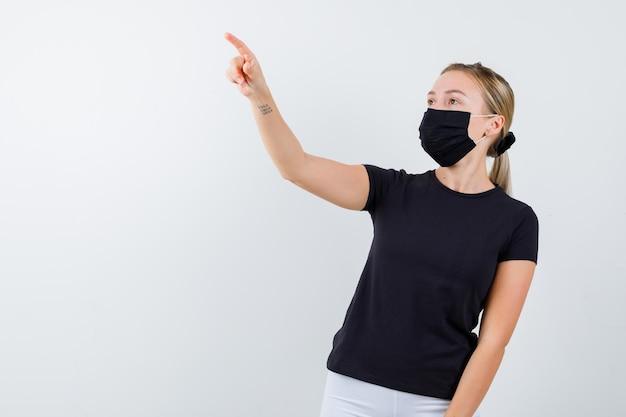 Giovane donna che indica via in maglietta, pantaloni, maschera medica e sembra sicura