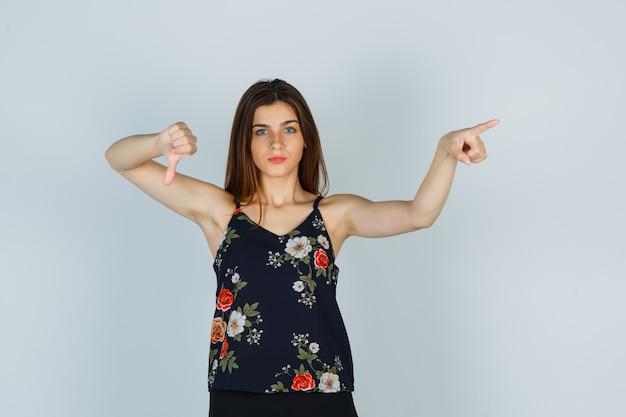 Giovane donna che punta via mentre mostra il pollice in giù in camicetta e sembra seria. vista frontale.