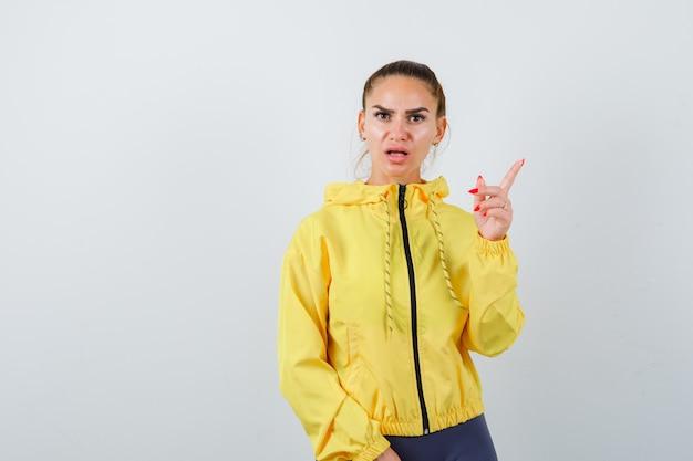 Giovane donna che punta in giacca gialla e sembra perplessa, vista frontale.