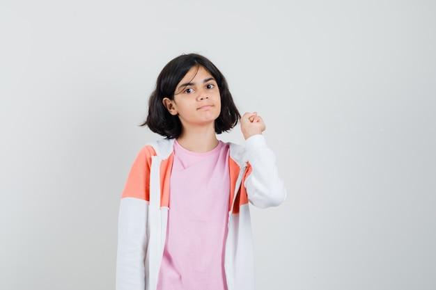 Молодая леди, указывая назад в куртке, розовой рубашке и выглядя спокойной.