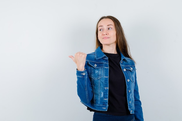 Giovane donna che punta indietro con il pollice in camicetta, giacca e sembra sicura, vista frontale.