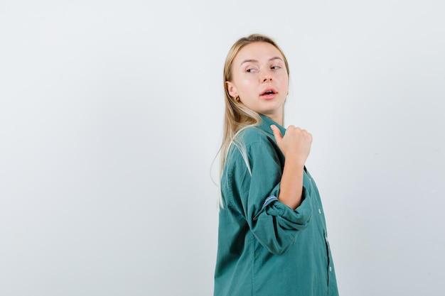 緑のシャツを着て親指で後ろを向いて自信を持って見える若い女性。 。