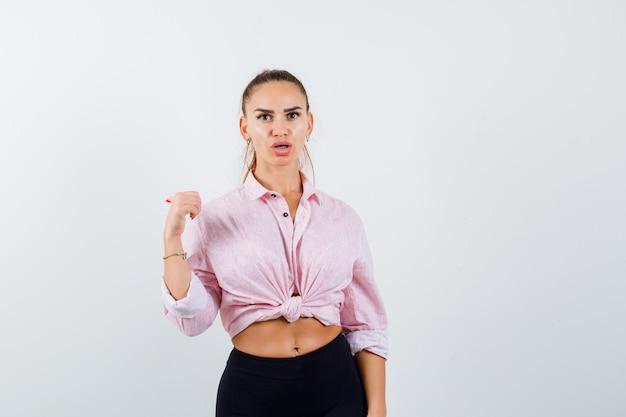 Giovane donna che indica indietro con il pollice in camicia, pantaloni e sembra scioccata. vista frontale.