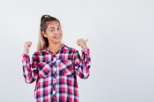 Giovane signora che indica indietro con i pollici in camicia controllata e che sembra allegra. vista frontale.