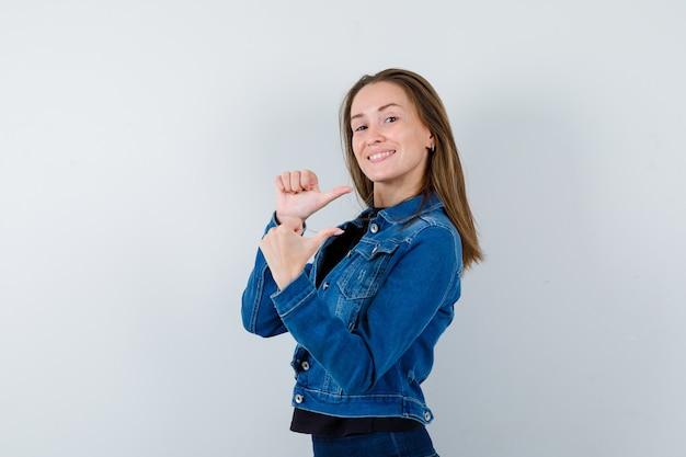 ブラウスに親指で後ろを向いて自信を持って見える若い女性。 。