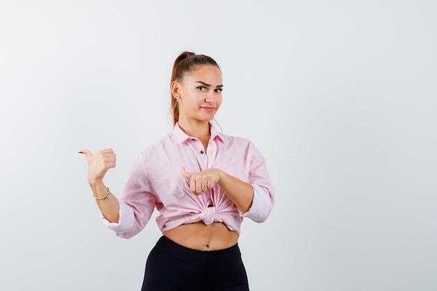 Giovane donna che indica indietro con i pollici in camicia, pantaloni e guardando fiducioso, vista frontale.