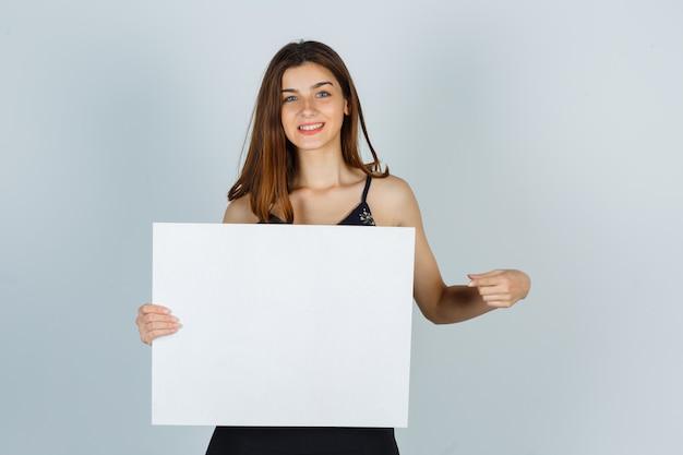 Giovane signora che indica tela bianca in camicetta e sembra allegra. vista frontale.