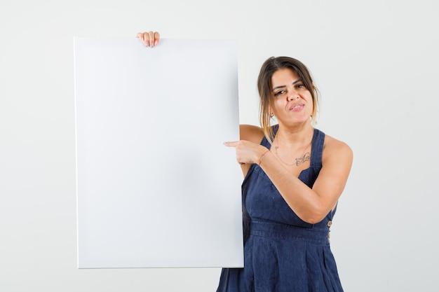 Giovane donna che indica una tela bianca in abito e sembra sicura