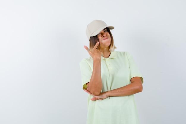 Giovane donna che punta alle guance soffiate in t-shirt, berretto e sembra divertente. vista frontale.