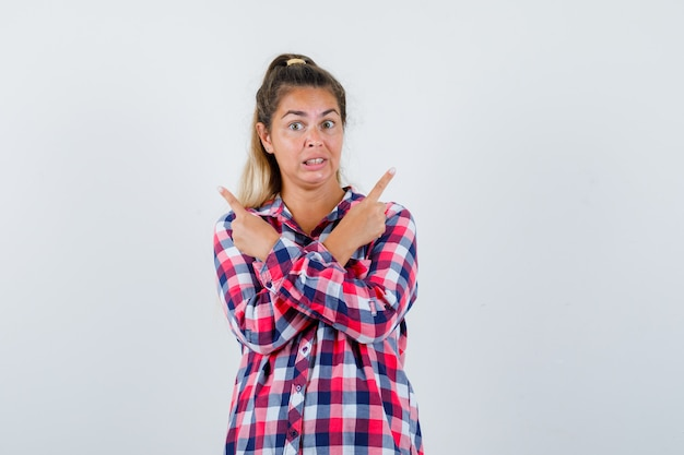 Young lady pointing to the both sides in checked shirt and looking troubled , front view.