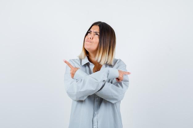 Giovane donna che indica entrambi i lati in una camicia oversize e sembra esitante, vista frontale.