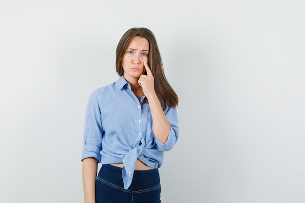 Young lady pointing at bottom lid of eye in blue shirt, pants and looking depressed