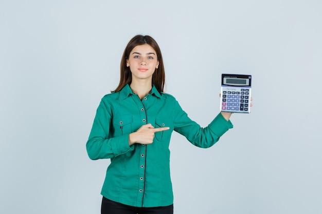 Giovane signora che indica alla calcolatrice in camicia verde e che sembra sicura. vista frontale.