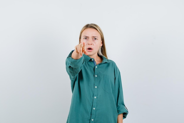 Young lady pointing at camera in green shirt and looking serious