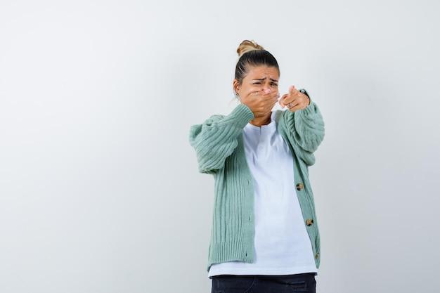 Tシャツ、ジャケット、怖い顔でカメラを指している若い女性