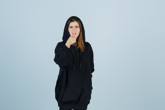 Young lady pointing camera in oversized hoodie, pants and looking angry. front view.
