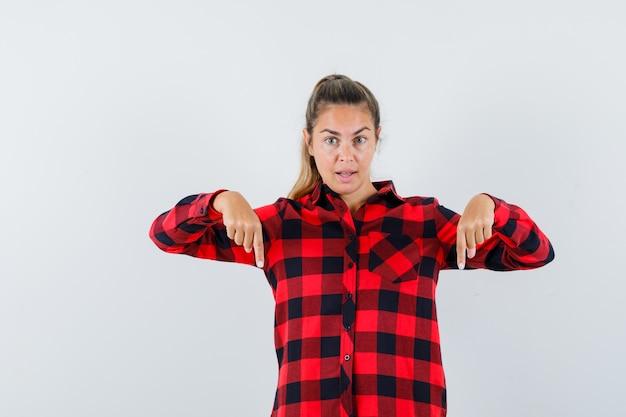 Giovane donna con la punta rivolta verso il basso in camicia casual e guardando fiducioso. vista frontale.