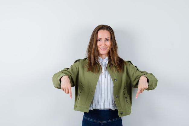 Giovane donna che punta verso il basso in camicia, giacca e sembra allegra, vista frontale.