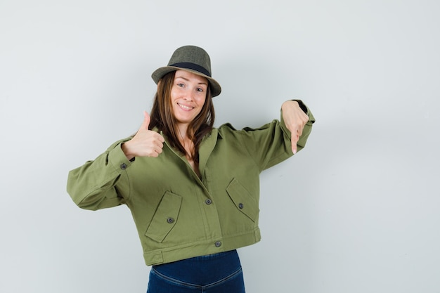 ジャケットのズボンの帽子で親指を上に示し、自信を持って見下ろしている若い女性