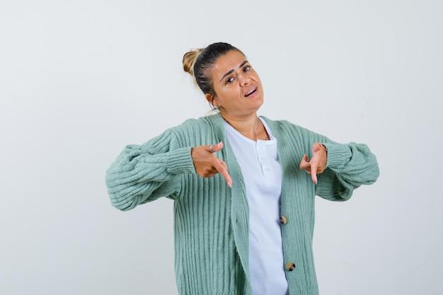 Giovane donna che punta verso il basso in maglietta, giacca e sembra sicura