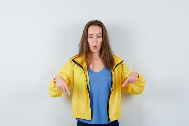 Giovane donna che punta verso il basso in maglietta e sembra stupita. vista frontale.