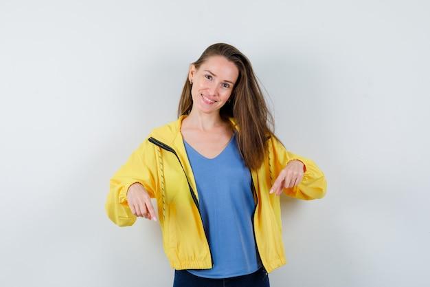 Giovane donna che punta verso il basso in maglietta e sembra allegra, vista frontale.
