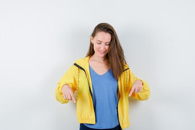 Giovane donna che punta verso il basso in t-shirt e sembra speranzosa, vista frontale.