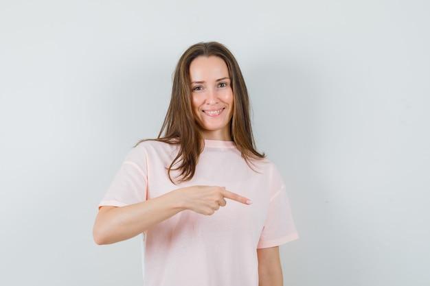 ピンクのtシャツで指を下に向けて、うれしそうに見える若い女性