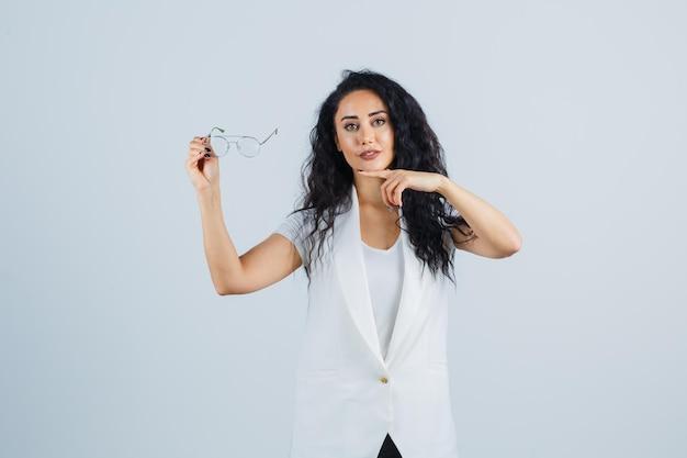 Giovane donna che punta agli occhiali in maglietta bianca, giacca e sembra sicura, vista frontale.
