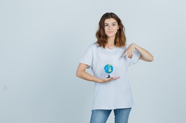 Tシャツ、ジーンズを保持し、自信を持って、正面図を見て地球を指している若い女性。