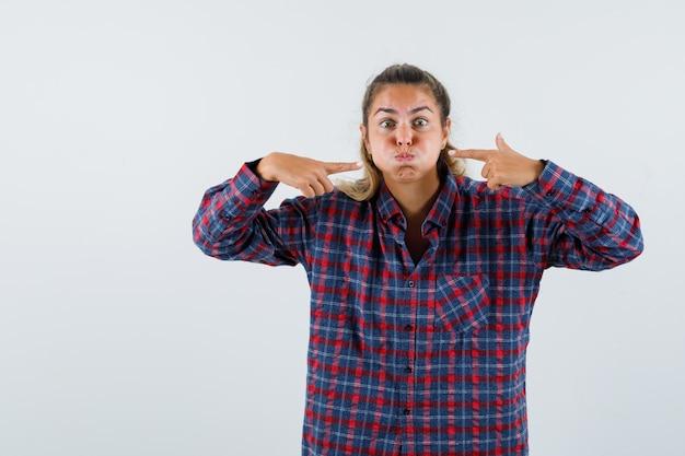 Giovane donna che indica le sue guance soffiate in camicia a quadri e sembra divertente, vista frontale.