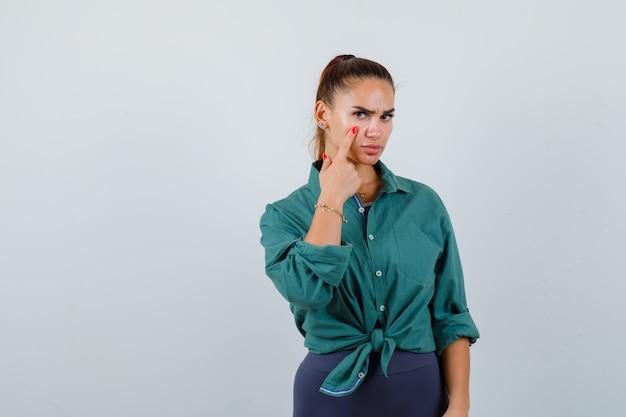 Giovane donna che indica la sua palpebra in camicia verde e sembra sconvolta. vista frontale.