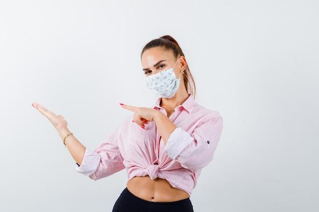 Giovane donna che indica il suo palmo aperto da parte in camicia, maschera e guardando fiducioso, vista frontale.
