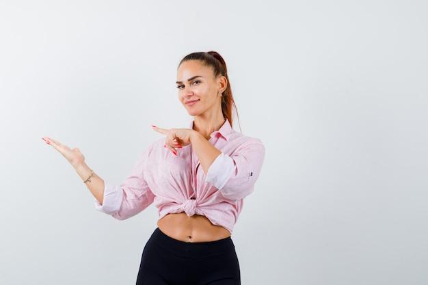 Giovane donna che indica il suo palmo aperto da parte in camicia, pantaloni e sembra sicura. vista frontale.