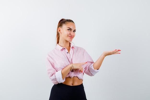 Giovane donna che indica il suo palmo aperto da parte in camicia, pantaloni e sembra allegra. vista frontale.